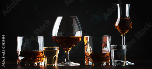 Fotobehang Alcohol Set of strong alcoholic drinks in glasses and shot glass in assortent: vodka, rum, cognac, tequila, brandy and whiskey. Dark vintage background, selective focus