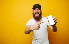 Amazed Young Bearded Man In White T-shirt Pointing At Phone