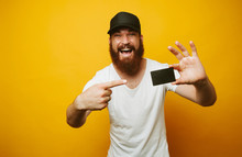 Portrait Of A Cheerful Bearded Man Pointing Finger At Credit Card Isolated Over Yellow Background