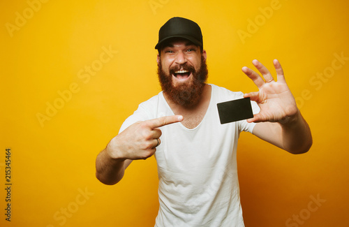 Fototapeta Portrait of a cheerful bearded man pointing finger at credit card isolated over yellow background obraz