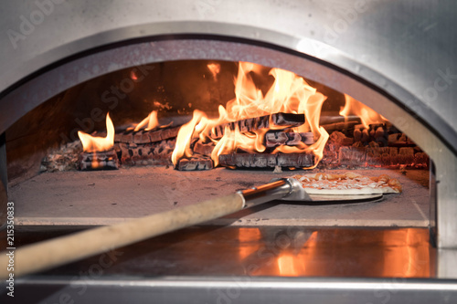 The working furnace for preparation of pizza. Inside burns firewood and big fire rises, on a shovel in the furnace put cheese pizza. Reflections of a flame on a surface