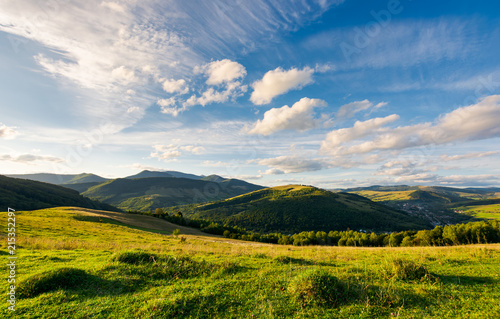 Fotobehang Bleke violet beautiful landscape in afternoon. gorgeous blue sky with golden clouds over the mighty mountain ridge in the distance. magical moment of nature
