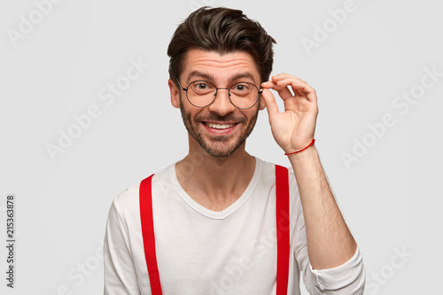 Photo  Glad stylish hipster with broad smile, wears spectacles, white casual sweater and red braces, happy to have weekend, stands against white background