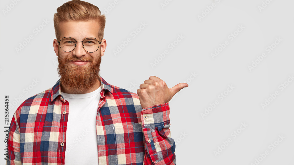 Fototapety, obrazy: Cheerful bearded male has charming smile, points aside, shows nice place to visit, attracts your attention, dressed in stylish clothes, has trendy hairstyle. People, style, advertisement concept