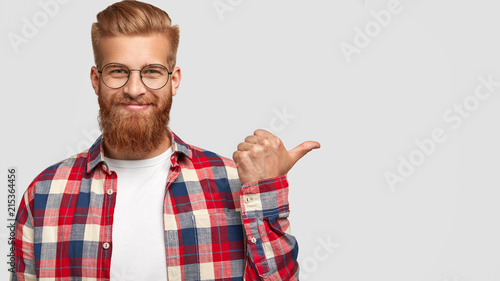 Canvas Print Cheerful bearded male has charming smile, points aside, shows nice place to visit, attracts your attention, dressed in stylish clothes, has trendy hairstyle