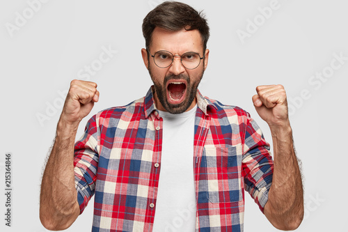Furious angry man with irritated expression, clutches fists angrily, shouts at someone, wears checkered shirt, stands against white background. Negative human emotions and feelings. Body language