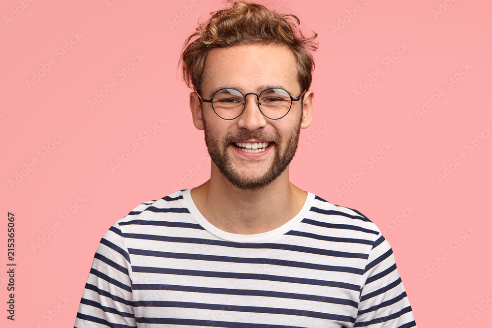 Fototapeta Positive young Caucasian male with pleasant friendly smile, shows white teeth, rejoices new stage in life, wears casual striped sweater and round spectacles, stands alone against pink background.
