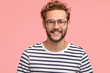 Positive young Caucasian male with pleasant friendly smile, shows white teeth, rejoices new stage in life, wears casual striped sweater and round spectacles, stands alone against pink background.