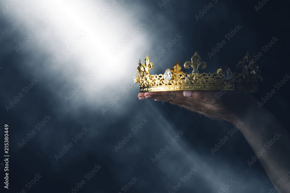 Fototapeta mysteriousand magical image of woman's hand holding a gold crown over gothic black background. Medieval period concept.