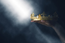 Mysteriousand Magical Image Of Woman's Hand Holding A Gold Crown Over Gothic Black Background. Medieval Period Concept.