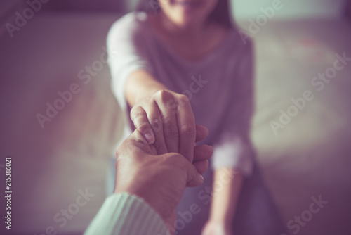 Fotografering  Man giving hand to depressed woman,Psychiatrist holding hands patient such as ma