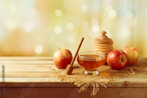Honey and apples on wooden table.