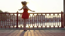 Cute Blonde Girl In Red Dress Looking At Sunset. Person On The Bridge. . The Sun Is Shining Through The Hair A Happy Woman Is Spinning On The Bridge. Slow Motion