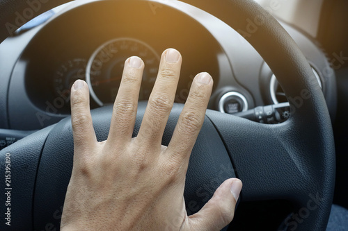 Fotografia  Driver is putting horn on steering during rush hour.