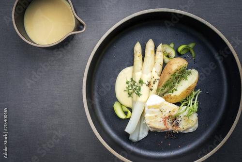 Modern Style deutsch gebratenes Barsch Fisch Filet mit weißen Spargel in Hollandaise Sauce und Pellkartoffel als Draufsicht auf einem Teller