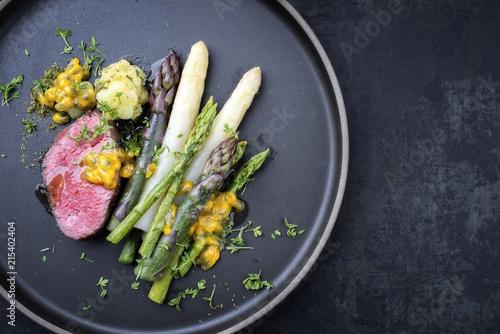 Modern Style deutsches Barbecue Filet Steak mit grünen, weissen und lila Spargel  als Draufsicht auf einem Teller mit Textfreiraum