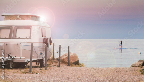 small, cute caravan by the sea, beach in backlight with sunflares Fototapeta
