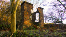 A Derelict Red Brick Building In A Forest.