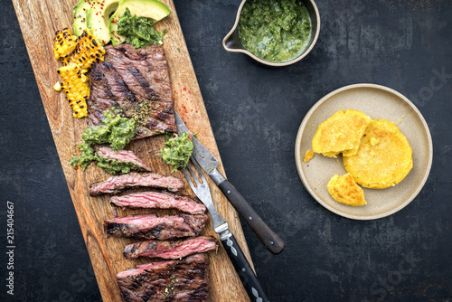 Barbecue South American dry aged wagyu flank steak with arepas, corn, and chimichurri sauce as top view on a cutting board