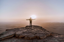 Alone Man In Israel Negev Desert Admires The View Of Sunrise. Young Male Person Stands On The Edge Of The Cliff