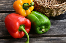 Mixed And Colorful Of Bell Pepper With Basket On Wooden Floor.
