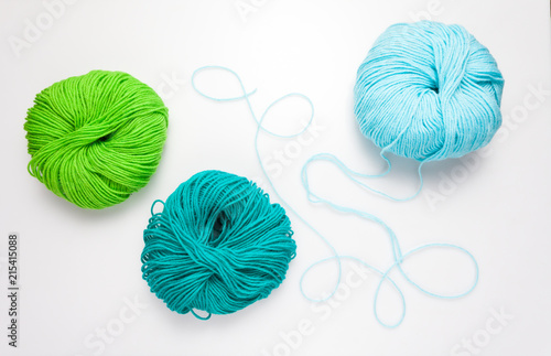 top view of colored yarn balls and knitting needles on white Canvas Print