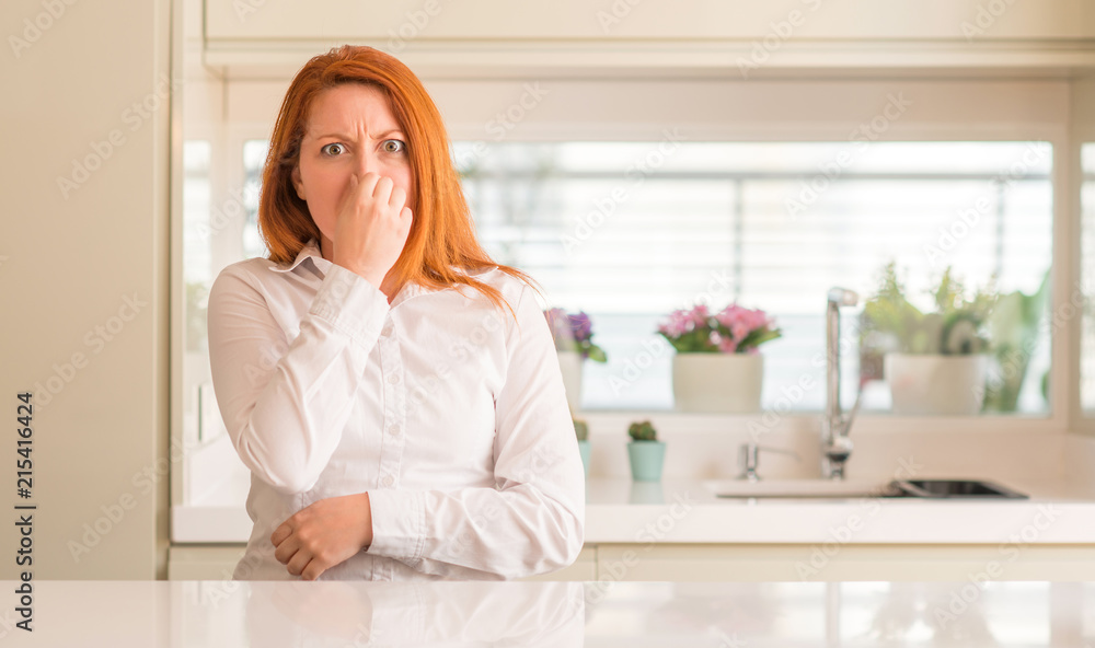 Fototapety, obrazy: Redhead woman at kitchen smelling something stinky and disgusting, intolerable smell, holding breath with fingers on nose. Bad smells concept.