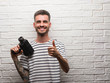 Young man filming holding video camera standing over white brick wall happy with big smile doing ok sign, thumb up with fingers, excellent sign