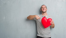 Young Caucasian Man Over Grey Grunge Wall Holding Red Heart With Surprise Face Pointing Finger To Himself