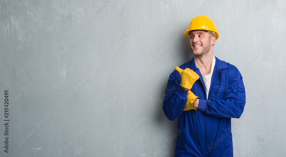 Fototapeta Young caucasian man over grey grunge wall wearing contractor uniform and safety helmet pointing and showing with thumb up to the side with happy face smiling