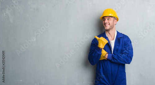 Fototapeta Young caucasian man over grey grunge wall wearing contractor uniform and safety