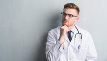 Young Redhead Doctor Man Over Grey Grunge Wall Serious Face Thinking About Question, Very Confused Idea