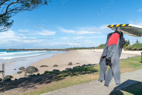 Fotografie, Obraz  Black and red wetsuit hanging from back of vehicle drying in sun on Duranbah Beach, Coolangatta