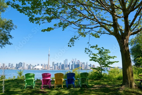 Panorama of Toronto, Canada over chairs different colours and tree from Isand on sunny day