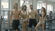 A group of athletes demonstrates a figure in the gym with healthy and beautiful bodies and smiles, young women and men of athletic build demonstrate their tightened bodies in the gym, train people
