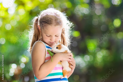 Child with guinea pig. Cavy animal. Kids and pets.