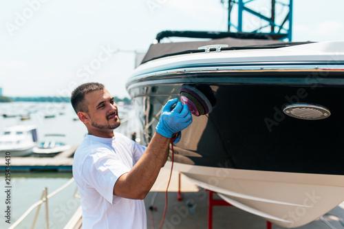 Boat maintenance - Man with orbital polisher polishing boat in marina.