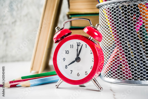 Fotografija  Back to school background with old books, alarm clock, pencils