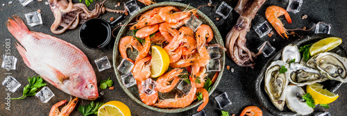 Fototapeta Fresh raw seafood squid shrimp oyster mussels fish with spices of herbs lemon on dark rusty background copy space top view obraz