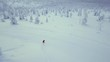 Snowboarder riding down powder snow during midwinter in Lapland Finland.