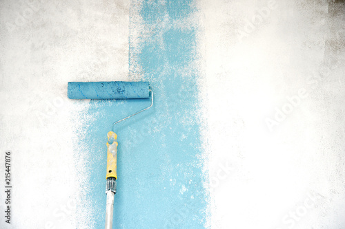 Blue Color With Paint Roller On White Cement Wall Under Construction Building Background