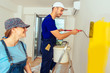 Workman with paint stick roller coloring walls with yellow color
