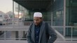portrait of young businessman texting on phone muslim man wearing kufi