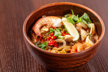Asian Oriental Cuisine. Japanese Spicy Soup With Seafood, Shrimps, Vegetables, Lime, Parsley, And Hot Pepper, In A Plate Of Red Clay, Stands On A Table In A Restaurant. Copy Space, Selective Focus