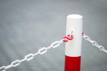 Metal Barrier Pole Painyed In Bright Red And White With White Chain Attached At Both Sides. Copy Space On Grey Background