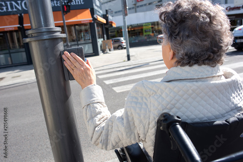 Fotografiet woman on the wheelchair pushing the crossing button