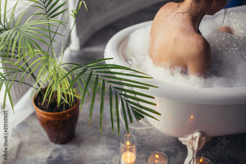 Fotografía woman is having shower in the bathroom with flower and candles on the floof