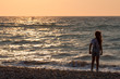 young girl from the back on the beach, sunset, sea, copy space