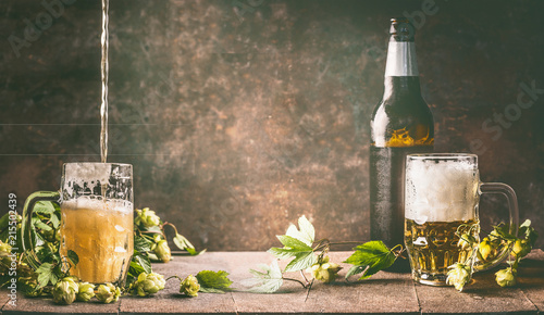 Spoed Foto op Canvas Bier / Cider Mug of beer with foam and cold bottle of beer with dew drops and hops vines on a rustic table opposite a dark wall background, front view