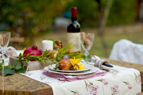 Lunch is romantic in autumn garden, atmosphere of holiday and coziness. Autumnal dinner in the open air with wine and fruit. Decor table with flowers and pomegranate. Vintage photo